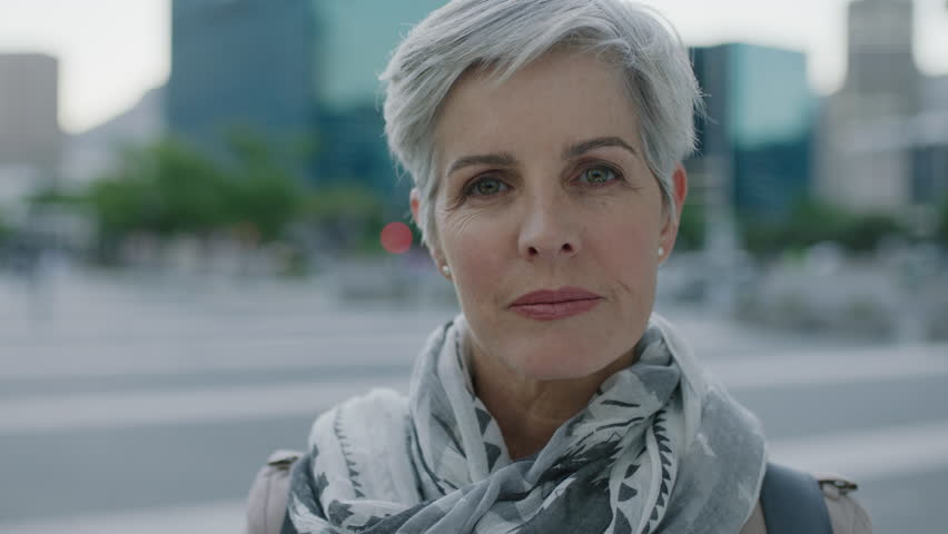 portrait of confident mature caucasian woman looking serious wearing scarf in urban city background modern lifestyle #1008369637