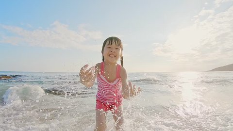 cute girl playing happily on the beach