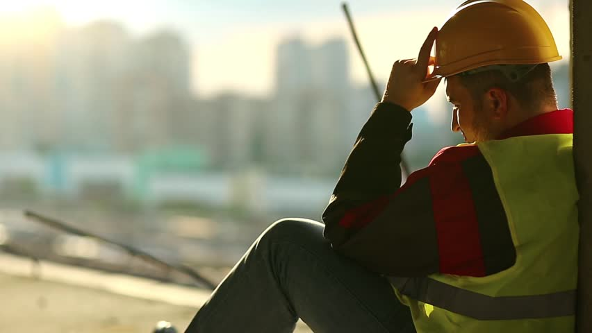 Builder sits on the floor and looks ahead. Worker rests on construction site. Constructor in yellow hard hat sits on concrete floor on project site Royalty-Free Stock Footage #1008372034