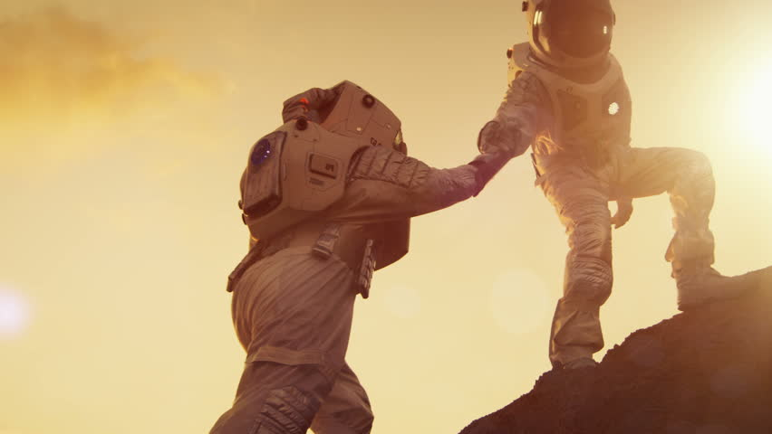Two Astronauts Climbing Mountain Hill Helping Each Other, Reaching the Top. Helping Hand. Overcoming Difficulties, Important Moment for the Human Race. Shot on RED EPIC-W 8K Helium Cinema Camera.