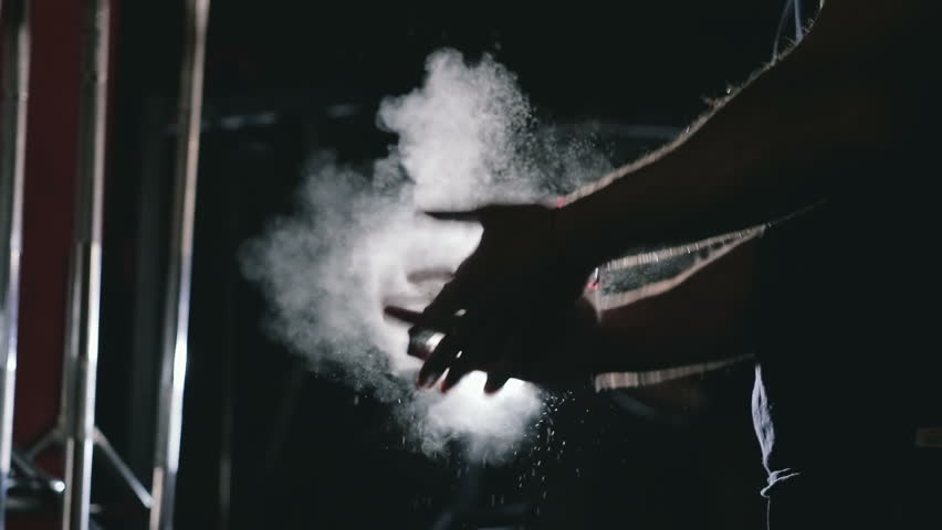 The athlete is preparing to lift the bar, hands shake magnesia in a dark room | Shutterstock HD Video #1008374476