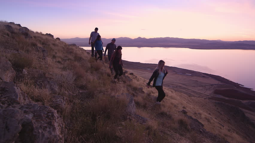 Group of millennials slowly hiking down mountainside during colorful sunset overlooking lake | Shutterstock HD Video #1008378916