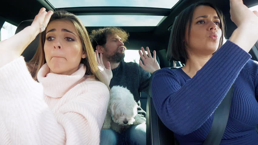 Happy women dancing with man in car driving happy slow motion