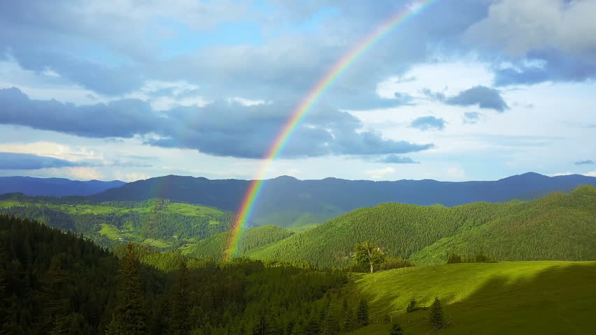 Aerial view of rainbow in the mountains, flying in a rainbow in the rain, aerial view of Rainbow in mountain landscape, Rainbow in the Mountains and Dramatic Mountain Clouds After the Rain