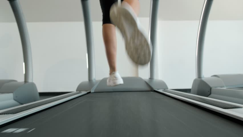A close up of a woman running on a treadmill fast run. White sneakers shoes sport. Female runner training fast athlete | Shutterstock HD Video #1008410383