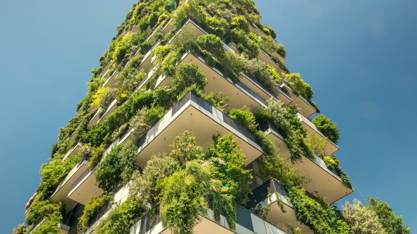 Modern ecological building, vertical gardens, terraces with trees and plants. Tilt up shot.