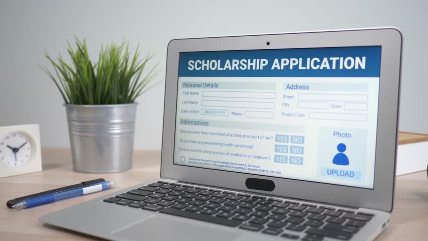 Scholarship application form showing on a laptop computer screen sitting on a desk. Camera is slowly turning around the computer.