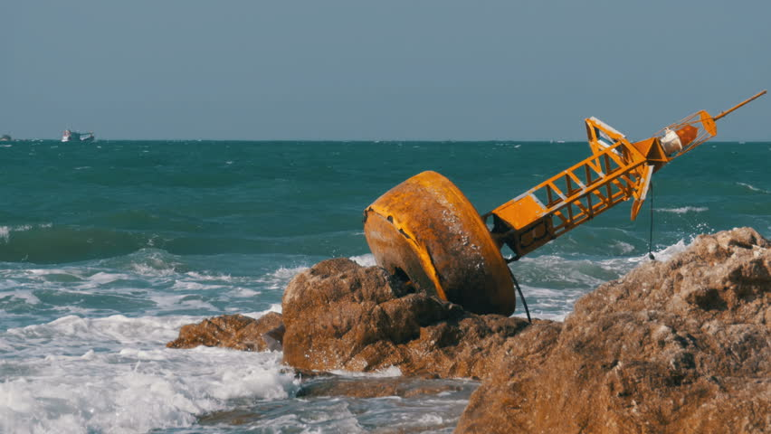 Old Rusty Yellow Buoy Lies on the Shore of a Rocky Beach. The waves beat against the rocks. Beautiful seascape. Thailand. Pattaya. Asia.