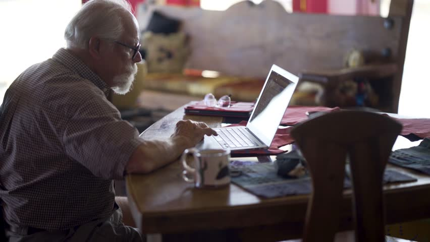 Backlit elderly man working on a laptop computer at a dining room table with coffee cup. | Shutterstock HD Video #1008419374