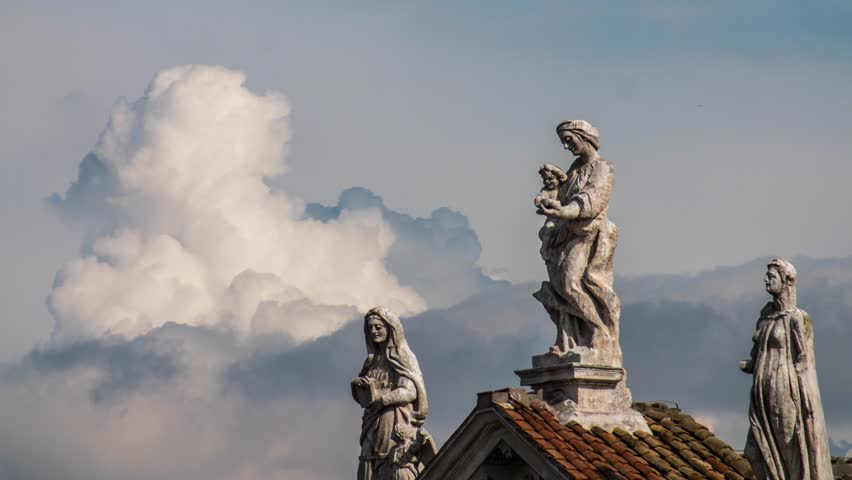 Incredible timelapse of the Virgin Mary statue and surrounding Saint statues on the roof of the Basilica di Santa Francesca Romana with clouds exploding in the background