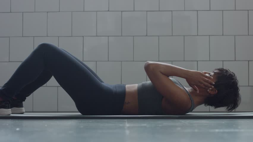 Side view dolly video of black woman makes an abs routin on the floor i synny loft Helthy fitness workout routine   Shutterstock HD Video #1008432034