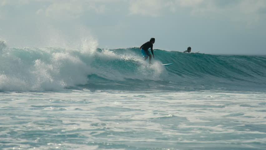 Panning clip of surfer riding a waves blue ocean. Balangan Beach, Bali, Indonesia - January 2018   Shutterstock HD Video #1008442876