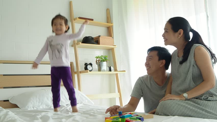 Asian family with happy time at home,daughter dancing and jumping on bed and parent sing a song.   Shutterstock HD Video #1008451102