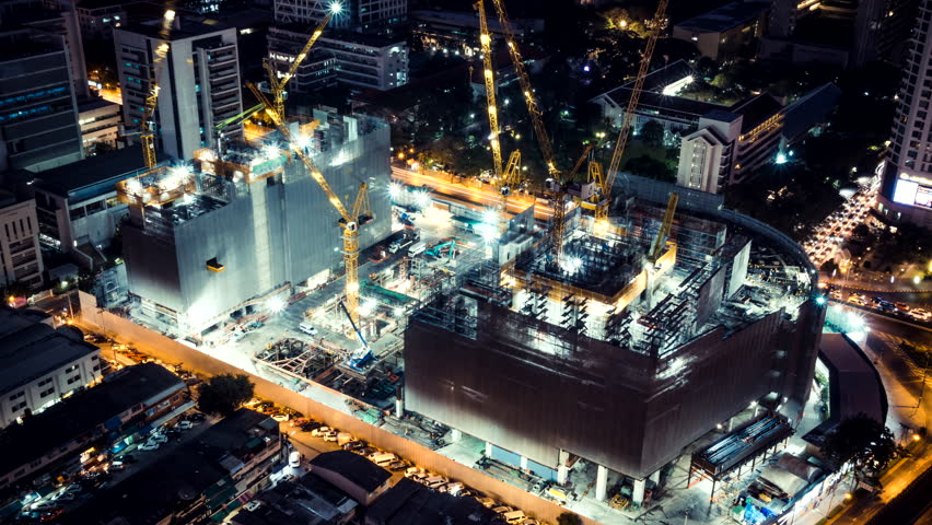 Time-lapse of construction site at night with light trails of traffic in the city, top view. Advanced building technology, busy metro downtown cityscape, or developing industrial country concept.