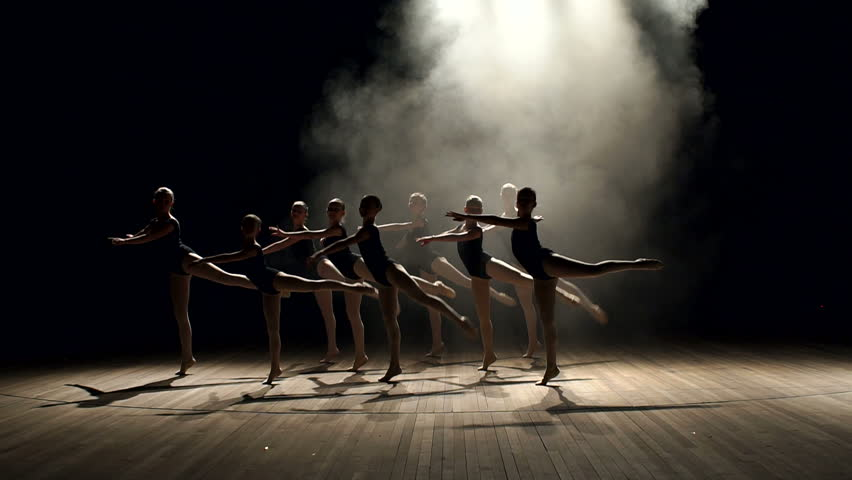 Young teen girls perform ballet on stage in smoke on black background. A choreographed dance of a group of graceful pretty young ballerinas practicing on stage in a classical ballet school.