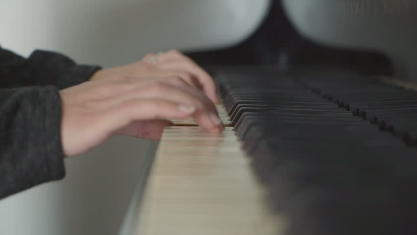 Girl playing the piano in her room, arpeggios with left hand.