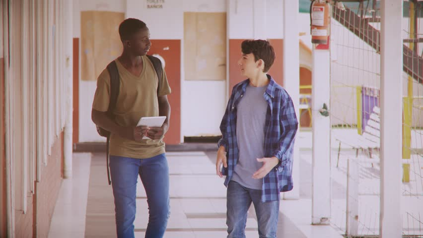 Couple of male teenagers happy and smiling while walking on school hallway, vintage filter. | Shutterstock HD Video #1008463858