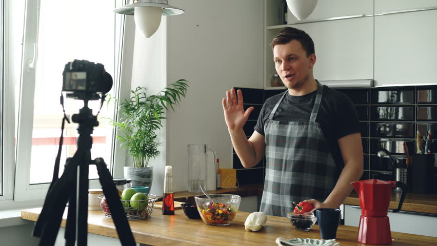 Handsome guy recording video food vlog about healthy cooking on digital camera in the kitchen at home. Vlogging and social media concept Royalty-Free Stock Footage #1008477343