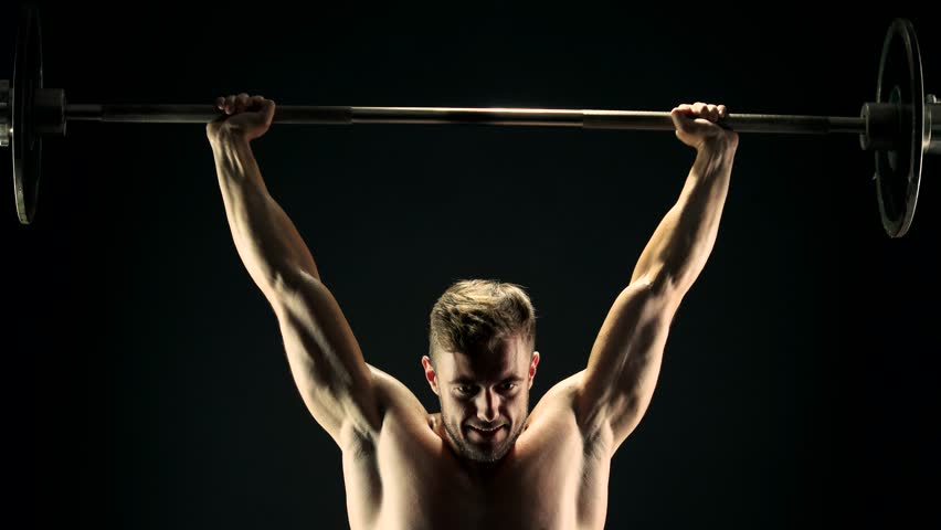 Young sportsman lifting heavy barbell. Hard training of professional sportsman, dark background. Power, strength and persistence.