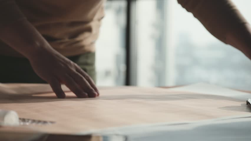Architect's desk: drawings, tape measure, ruler and other drawing tools. Engineer works with drawings in a bright office, close-up. Insturments and office for designer. Male hands draw with a pencil. #1008480172