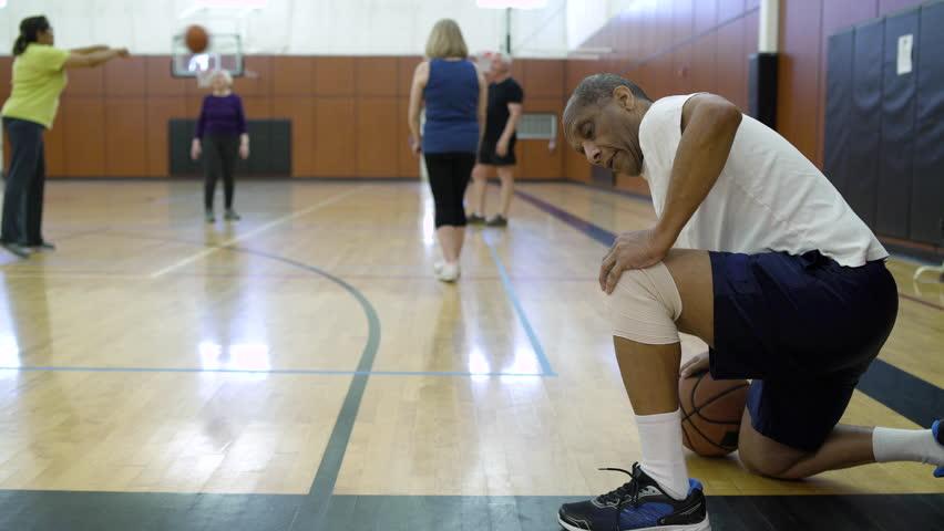 Mature man rubbing his knee on a basketball quart | Shutterstock HD Video #1008495376
