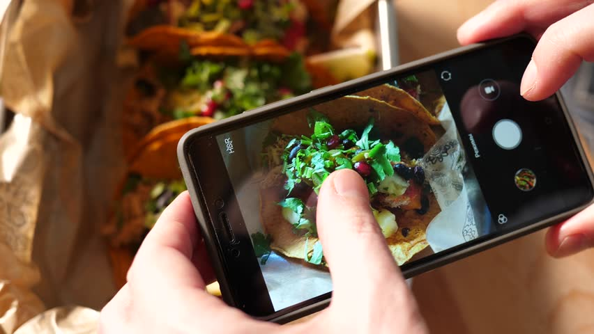 Food photo with a mobile phone a guy in Mexican cuisine restaurant takes pictures for social media #1008503356