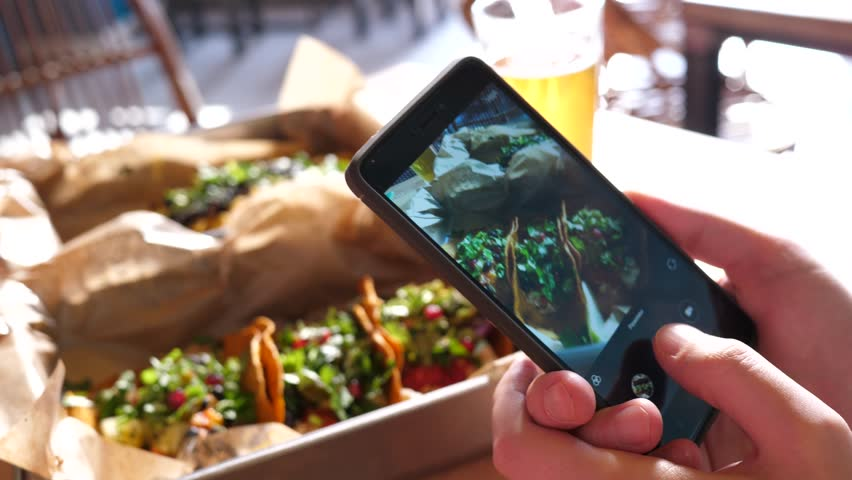 Food photo with a mobile phone a guy in Mexican cuisine restaurant takes pictures for social media #1008503359