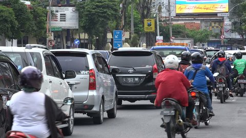 SURABAYA, INDONESIA - APRIL 2017: Motorbikes ride past cars stuck in traffic jam during rush hour Surabaya, Indonesia