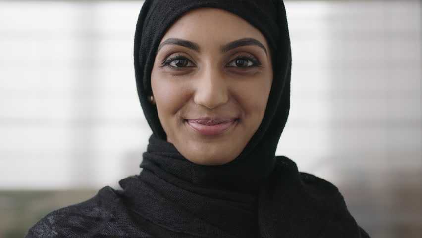 close up portrait of professional young muslim business woman looking at camera smiling happy wearing traditional headscarf in office background #1008513142