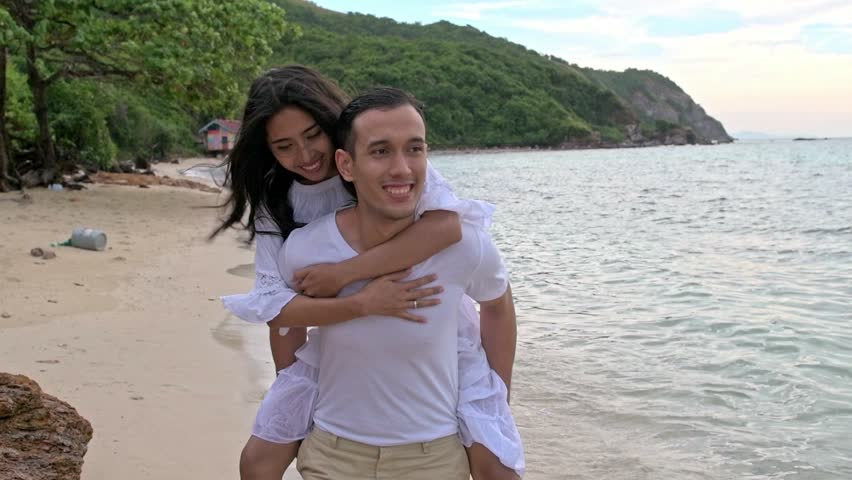 Attractive young couple having fun on beach. Running on beach. Young chinese woman with White man in early 20s. Mixed race. Shot in slow motion. Film look.