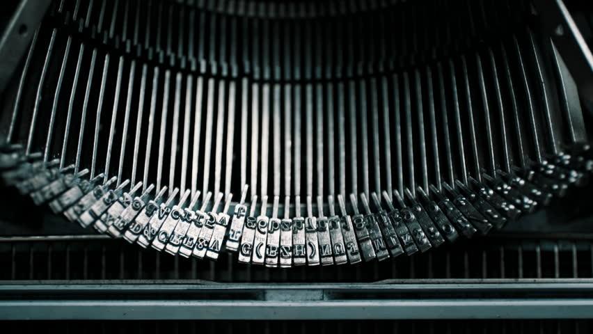 Slow motion closeup shot of detail of vintage typewriter metallic letters