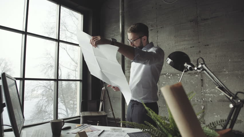 Bearded man (hipster) standing faces to panoramic window and looks at blueprints. Young architect in stylish loft office works with documents. Creative architect thinking on the big drawings.