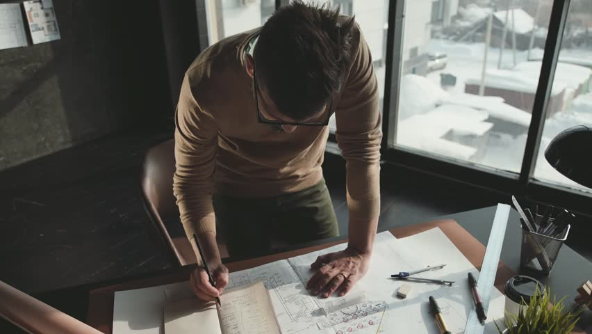 Hipster engineer works with blueprint. Shoot from above. Young architectural engineer working in office. Bearded man in glasses makes sketches. Loft style, minimalistic interior, drawings on the table | Shutterstock HD Video #1008551899