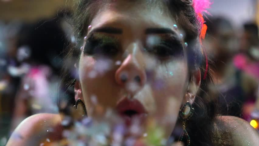 Girl blowing colorful confetti at Salvador Carnaval, Brazil
