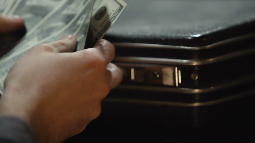 Hidden stash with money, man taking some dollars from suitcase, hand close-up | Shutterstock HD Video #1008573187