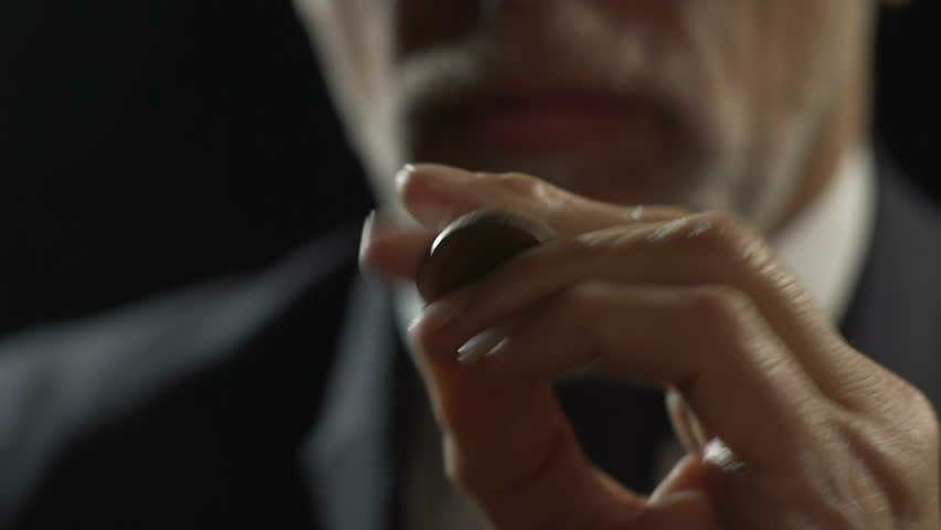 Adult man in eyeglasses making hand trick with coin, thinking about budget
