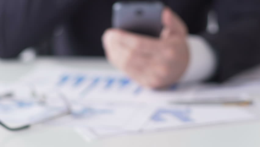 Investment analyst reading business news on smartphone, analyzing information | Shutterstock HD Video #1008577144