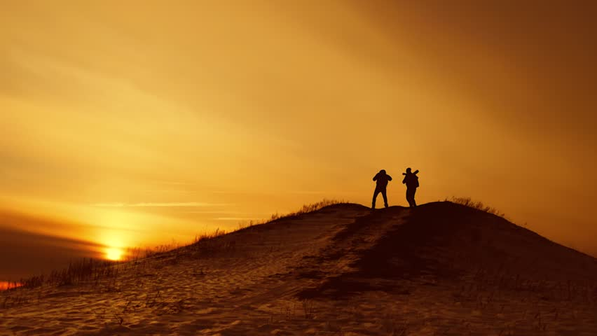 The Silhouette of two man standing on the top of mountain with Backpacks and other Gear expressing Energy and Happiness. Travel concept. | Shutterstock HD Video #1008586300