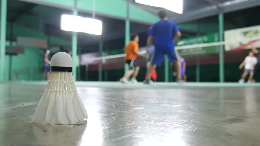White shuttlecock laying on the floor and a blurred background of badminton practice. Blurred background of badminton practice. Badminton practice inside the gymnasium.