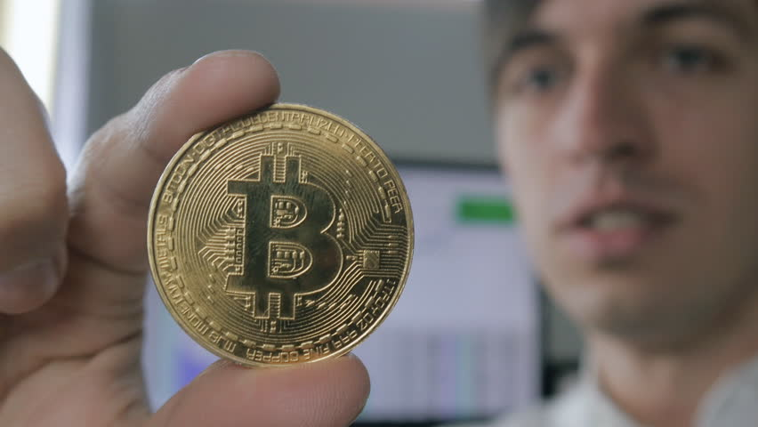 Close up of Amazed Surprised Young BusinessMan holds BTC Bitcoin in hand. Success on earnings in the crypto-currency market