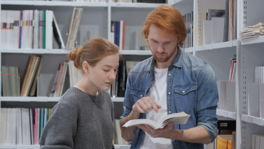 Positive Smiling Students Reading Book and discussing in Library Royalty-Free Stock Footage #1008600007