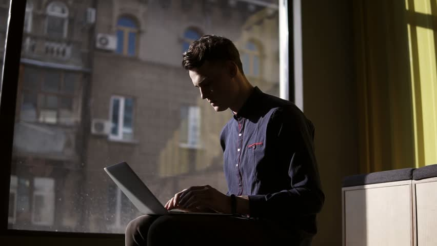 Attractive sexy young guy sitting near panoramic window typing something on his laptop. Work process.   Shutterstock HD Video #1008616066