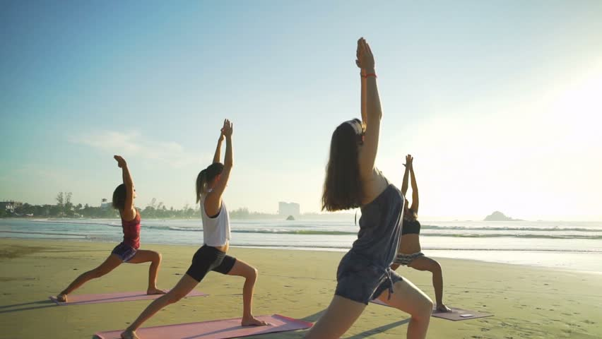 Group of woman do yoga warrior pose on the beach sunrise rapid slow motion