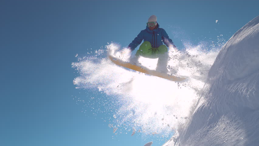 SUPER SLOW MOTION, LENS FLARE, CLOSE UP: Snowboarder jumping in powder snow on winter day in sunny mountains. Extreme freerider sprays fresh snow over bright winter sun while jumping high in the air.
