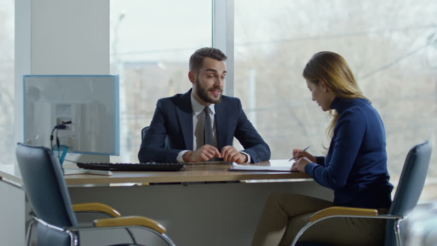 PAN of cheerful auto salesman in suit sitting at his desk and talking with happy female client signing purchase agreement, then giving her keys from new car and shaking hands