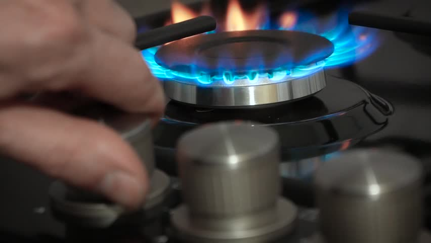 Person hand turns on kitchen cooktop gas burner and natural gas ignites burns with blue flame and then turned off.