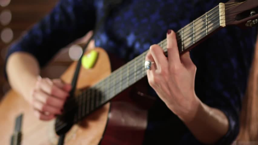 Hands on the strings of an acoustic guitar. Close-up. Focus sharpness moves from one hand to the other. A girl in a blue dress is playing a musical instrument.