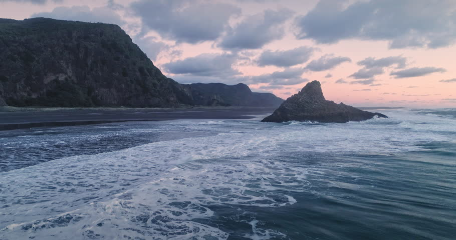 Aerial Flying rocky beach outcrop And crashing Waves At Karekare at sunset, Auckland, New Zealand