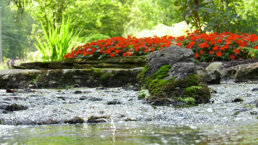 stream runs through beautiful garden low panning view 4k