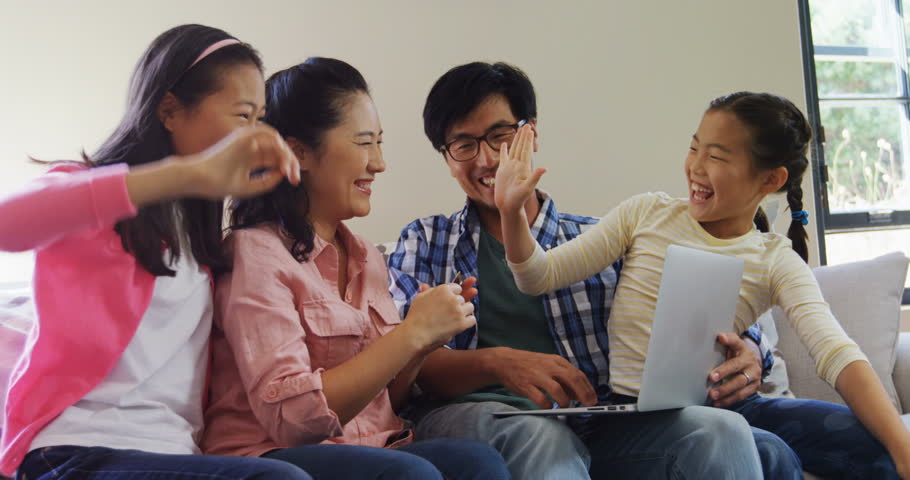 Family giving high five while using laptop in living room at home 4k | Shutterstock HD Video #1008655168